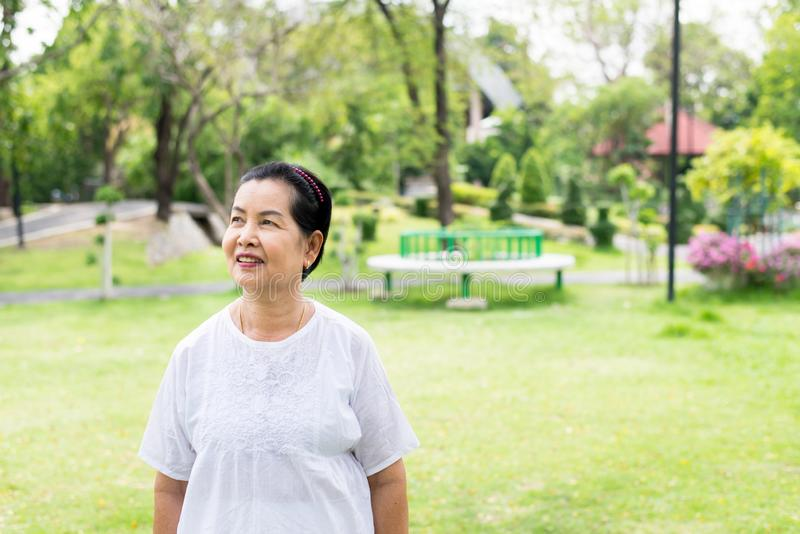 Portrait of a elderly asian woman standing and looking something at park,Happy and smiling stock photos
