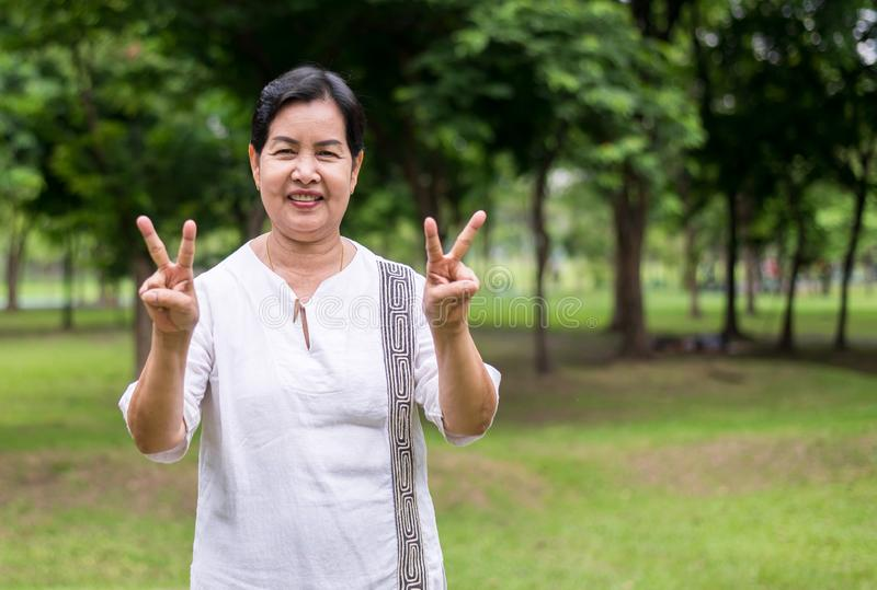 Portrait of a elderly asian woman standing and showing peace hand sing at park,Happy and smile face royalty free stock image