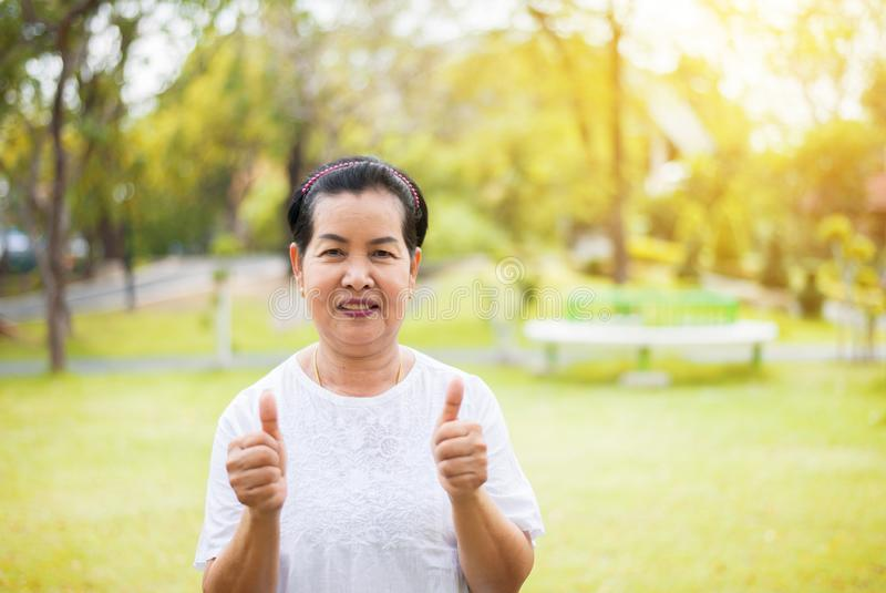 Portrait of a elderly asian woman standing and showing thumb up at park in the morning,Happy and smiling,Freedom time royalty free stock image