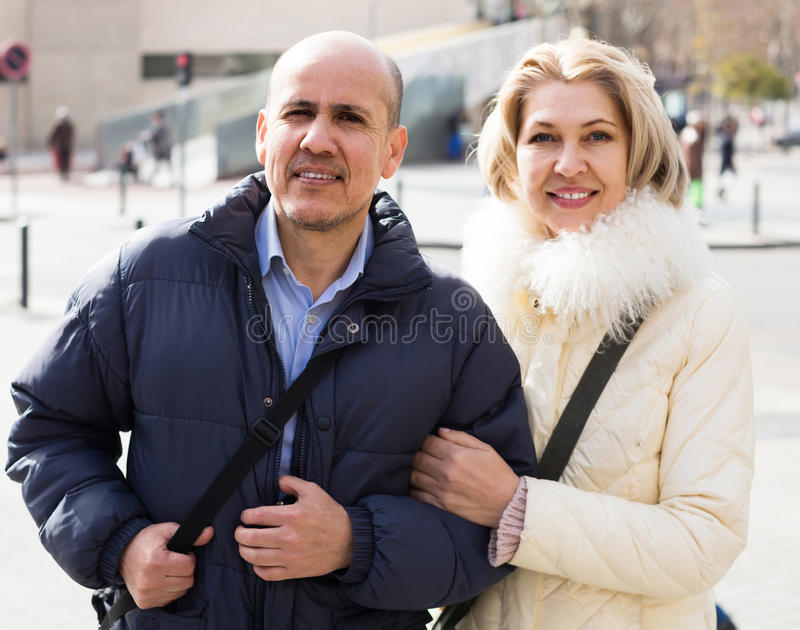 Portrait of elderly couple outdoor during date walking. Portrait of elderly american couple smiling outdoor during date walking. focus on man stock images