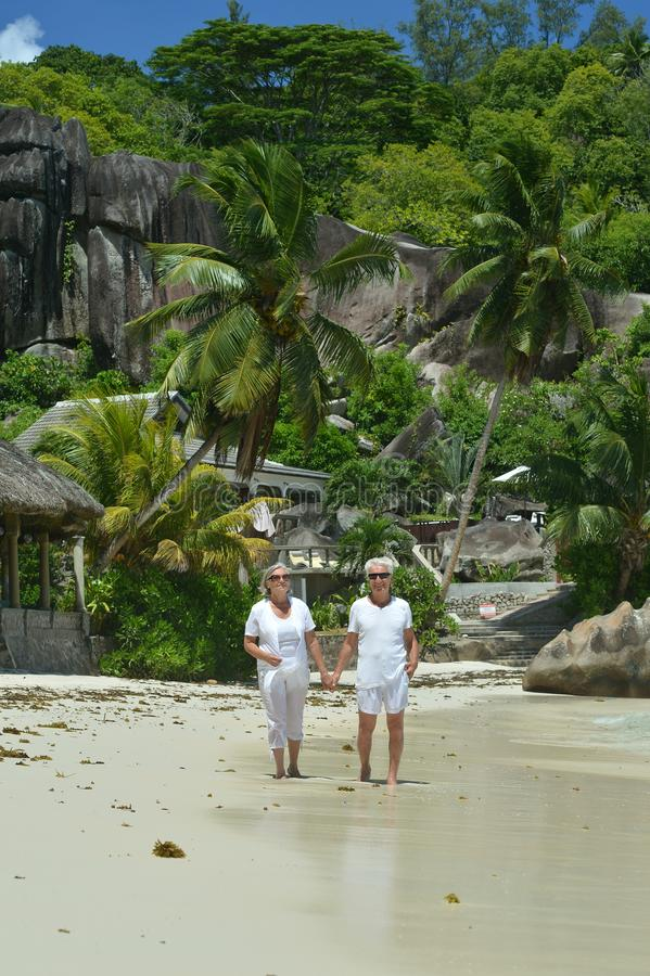 Portrait of elderly couple resting on tropical beach stock photos