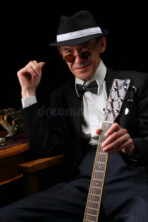 Portrait of an elderly jazz musician in retro style. With guitar and trombone royalty free stock photos