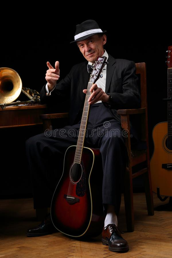 Portrait of an elderly jazz musician in retro style. With guitars and trombone royalty free stock photo