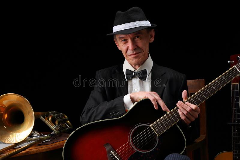 Portrait of an elderly jazz musician in retro style. With guitars and trombone royalty free stock image