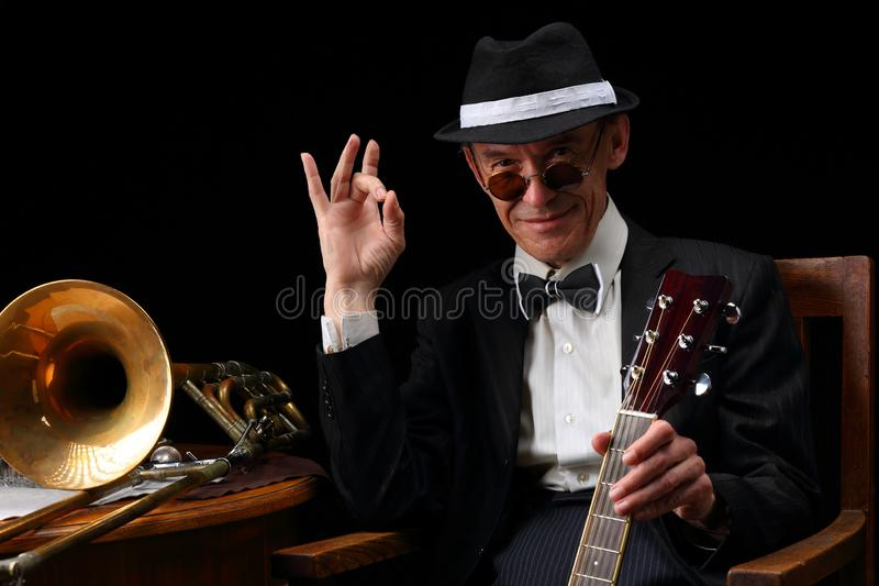 Portrait of an elderly jazz musician in retro style. With guitars and trombone royalty free stock photography