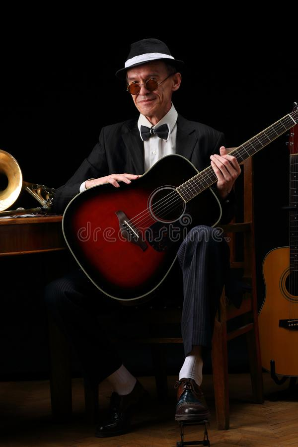 Portrait of an elderly jazz musician in retro style. With guitars and trombone stock images
