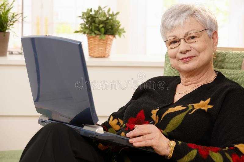 Portrait of elderly lady with computer. Smiling elderly lady holding laptop computer, sitting in armchair, smiling at camera royalty free stock image