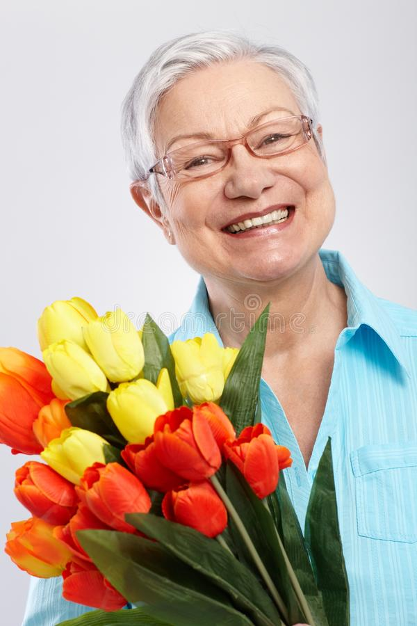 Portrait of elderly lady with flowers. Portrait of elderly lady with bouquet of fresh tulips, smiling royalty free stock photos