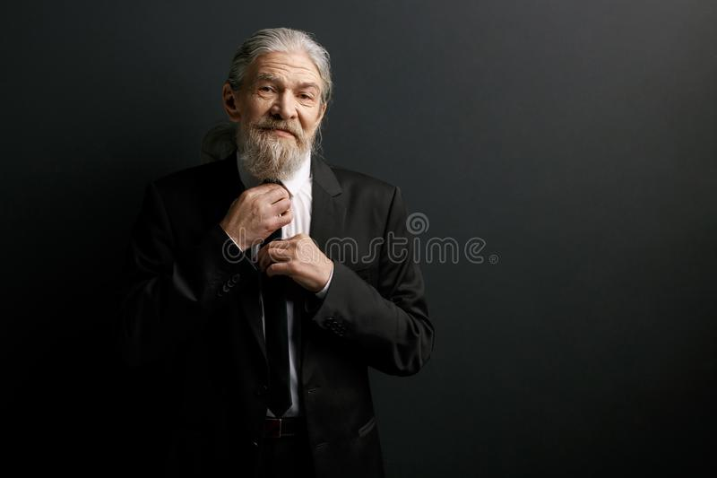 Portrait of an elderly man in black suit and white shirt. royalty free stock photo