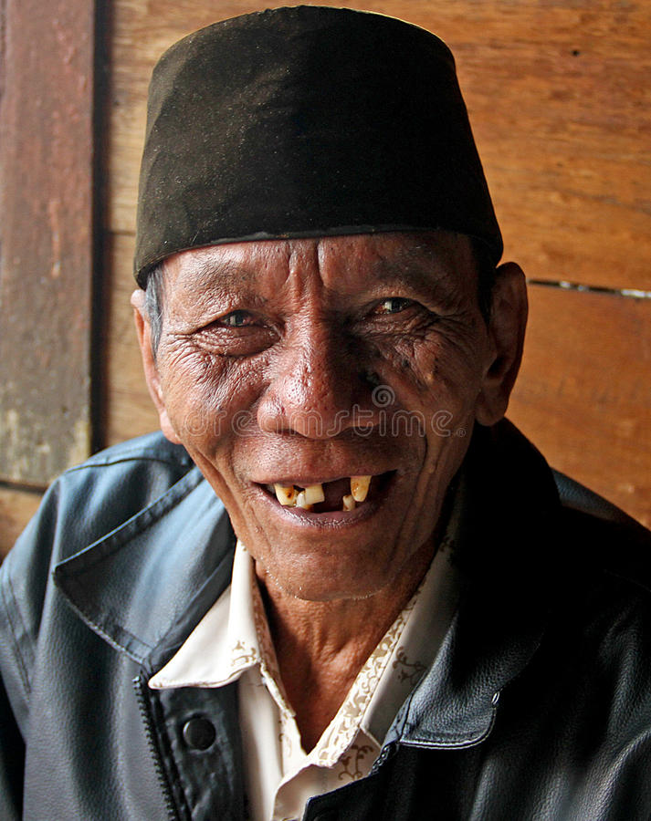 PORTRAIT OF ELDERLY MAN IN INDONESIA. A portrait of an elderly man in a wet market in the city of Padang in West Sumatra stock photo