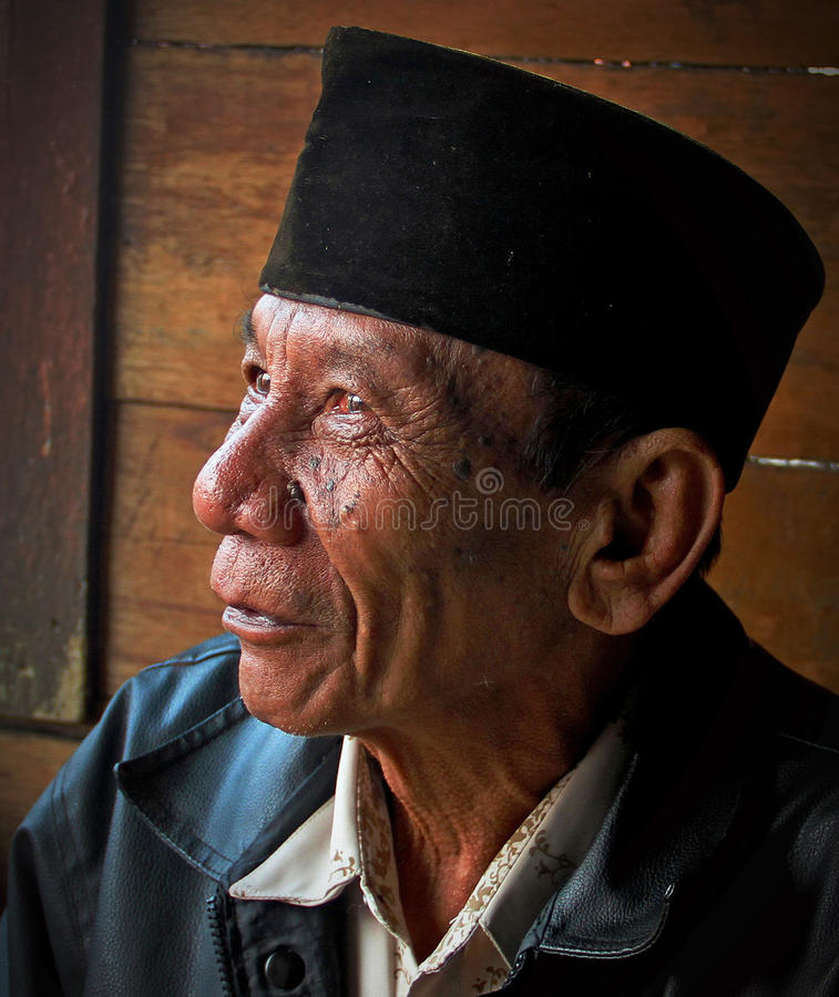 PORTRAIT OF ELDERLY MAN IN INDONESIA. A portrait of an elderly man in a wet market in the city of Padang in West Sumatra royalty free stock photo