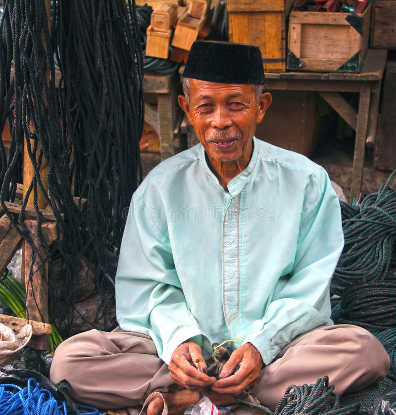 PORTRAIT OF ELDERLY MAN IN INDONESIA. A portrait of an elderly man in a wet market in the city of Padang in West Sumatra, Indonesia. This man is seller of rope stock photo