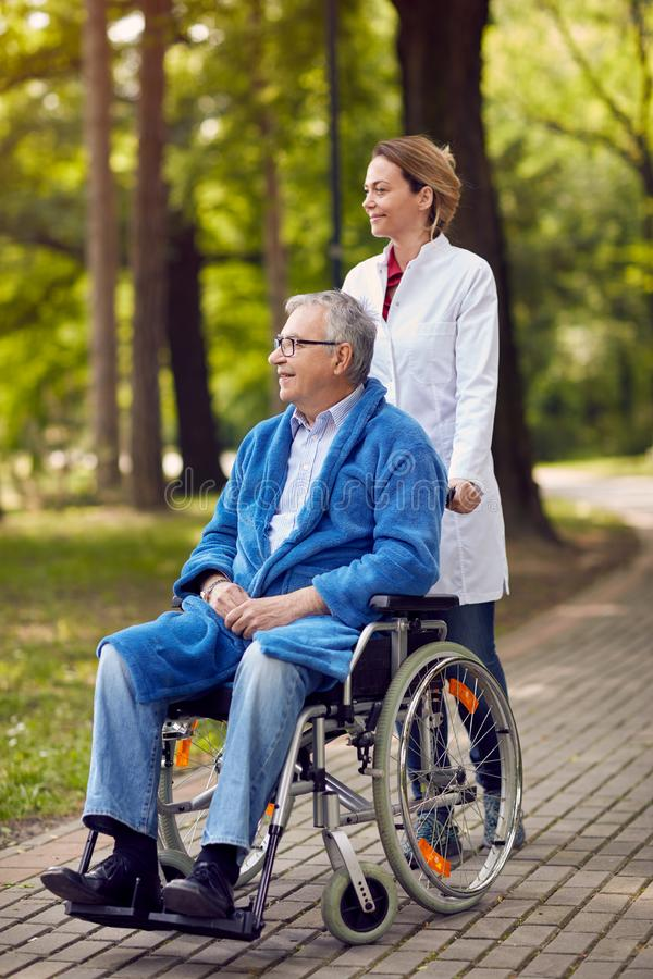 Portrait of elderly man on wheelchair with nurse outdoor royalty free stock photography