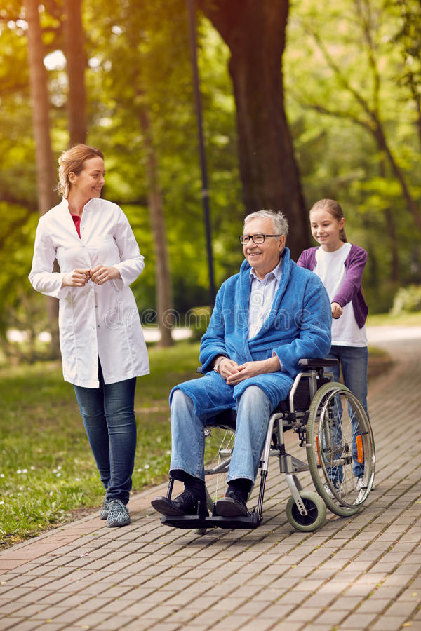 portrait of elderly man on wheelchair with nurse and granddaughter outdoor. stock image