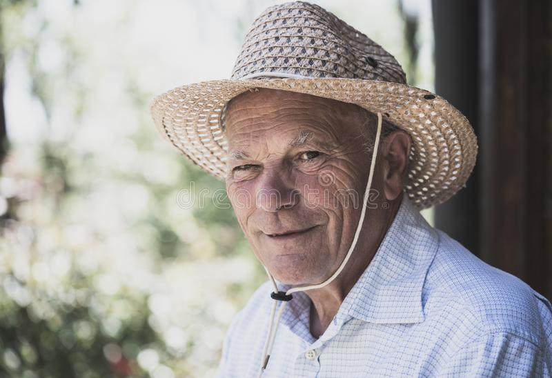 Portrait of elderly smiling man with straw hat looking at the cam royalty free stock images