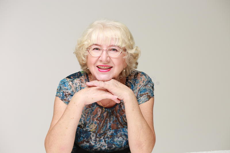Portrait of an elderly smiling woman. Light background royalty free stock image