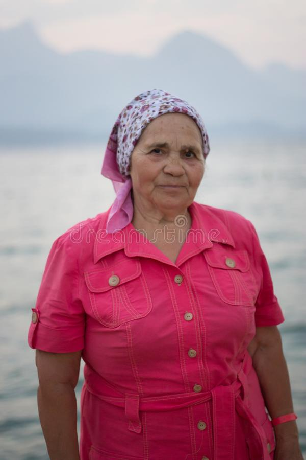 Portrait of elderly smiling woman by the sea on background mountains. Close up royalty free stock images