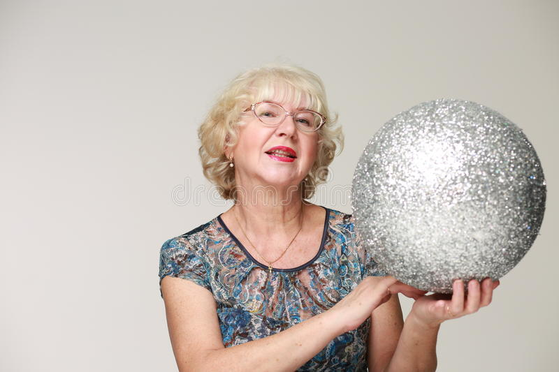 Portrait of an elderly smiling woman with a silver ball. Light background royalty free stock photo