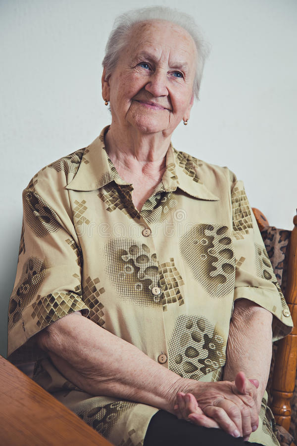 Portrait of an elderly smiling woman. Sitting on chair royalty free stock images