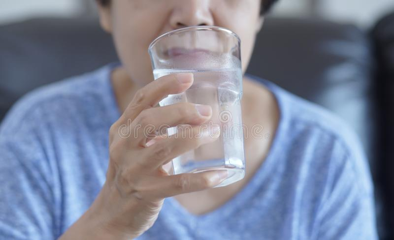 Portrait Elderly woman drinking glass of water to retirement i stock photos