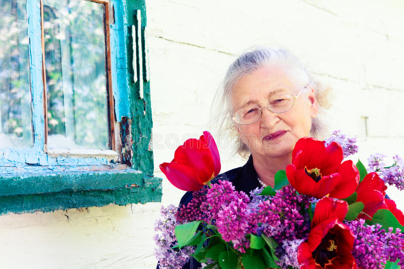 Portrait of an elderly woman with flowers royalty free stock photos