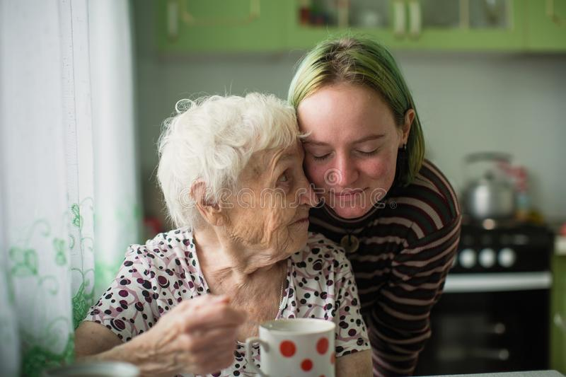Portrait of elderly woman with her granddaughter at the table in the kitchen. Love. Portrait of elderly women with her granddaughter at the table in the kitchen royalty free stock photo