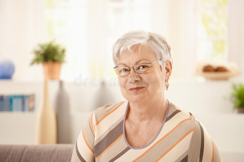 Portrait of elderly woman. At home, looking at camera, smiling stock photography