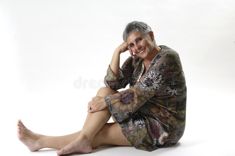 Portrait of an elderly woman sitting on the floor stock images