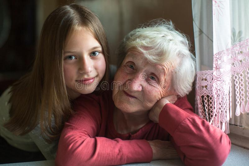 Portrait of an elderly woman with her young great-granddaughter. Love. Portrait of an elderly women with her young great-granddaughter stock images