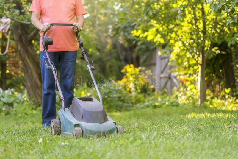 Portrait of eldery senior man working in the summer garden walking on a grass field royalty free stock image
