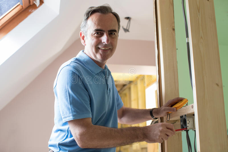 Portrait Of Electrician Installing Socket In New House stock photo