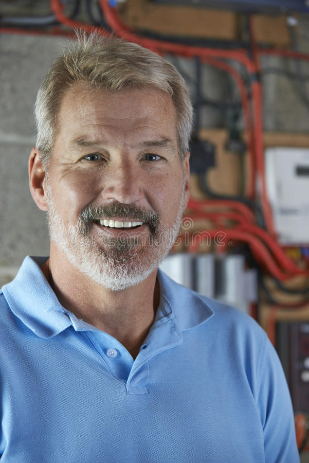 Portrait Of Electrician Standing Next To Fuseboard royalty free stock photography