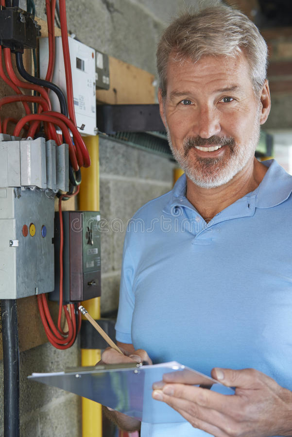 Portrait Of Electrician Standing Next To Fuseboard royalty free stock photos