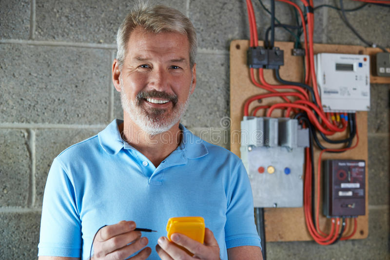 Portrait Of Electrician Standing Next To Fuseboard stock photos