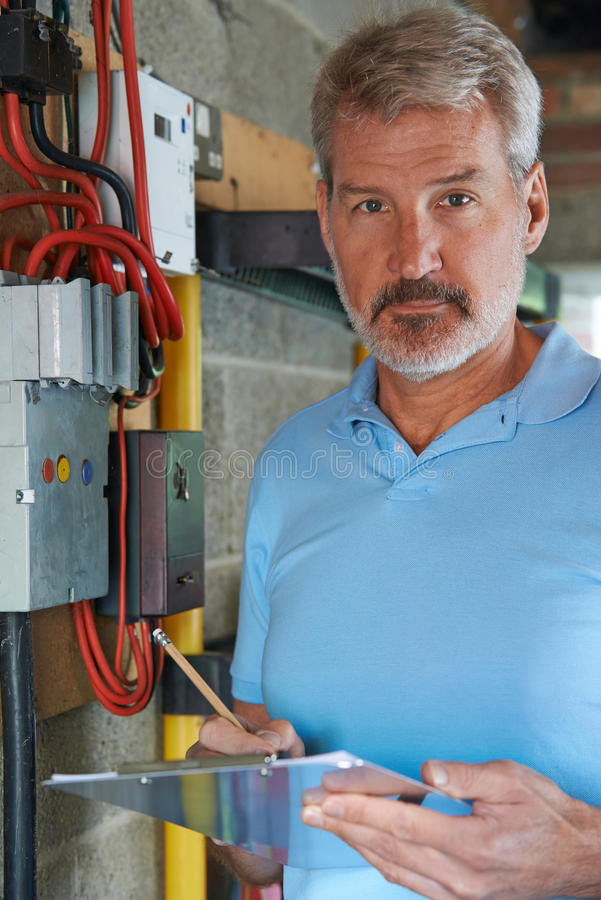 Portrait Of Electrician Standing Next To Fuseboard stock image