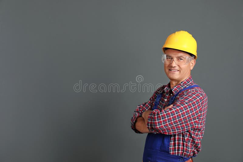 Portrait of electrician wearing uniform on gray background stock image