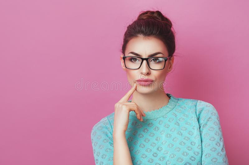 Portrait of elegance thoughtful woman having hair bun in bright skirt isolated on pink background touching chin and have a great i stock photography