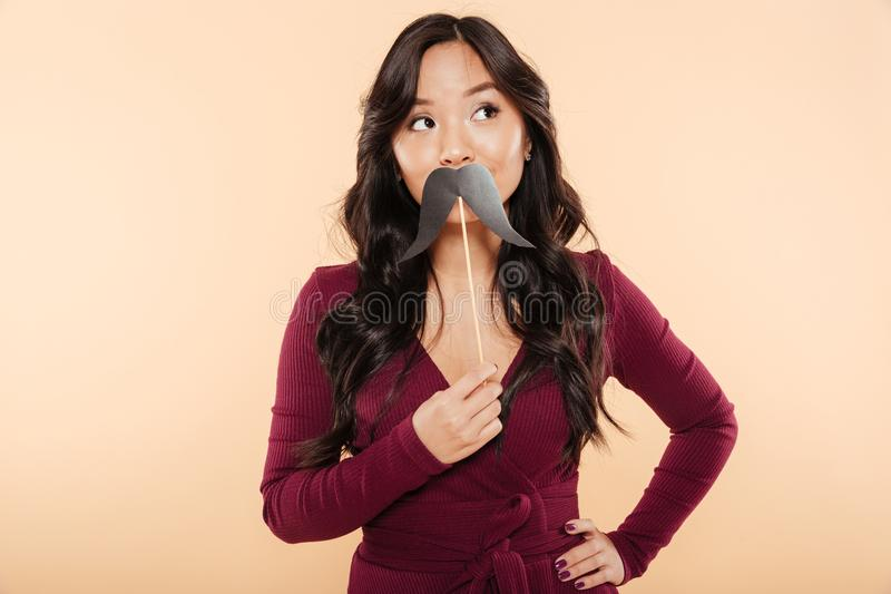 Portrait of elegant asian female in pretty maroon dress having f. Un on peach background, putting artificial mustaches over mouth stock photo