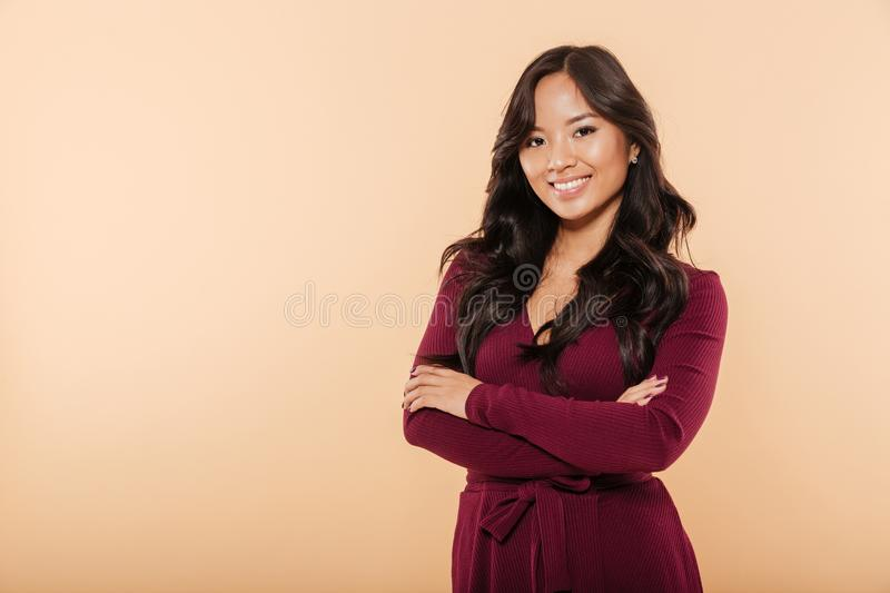 Portrait of elegant asian female in pretty maroon dress posing o. N camera with arms folded, over peach background stock photos