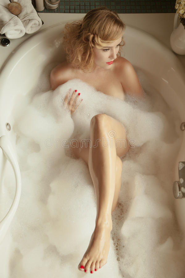 Elegant beautiful woman relaxing in a spa bath stock photography