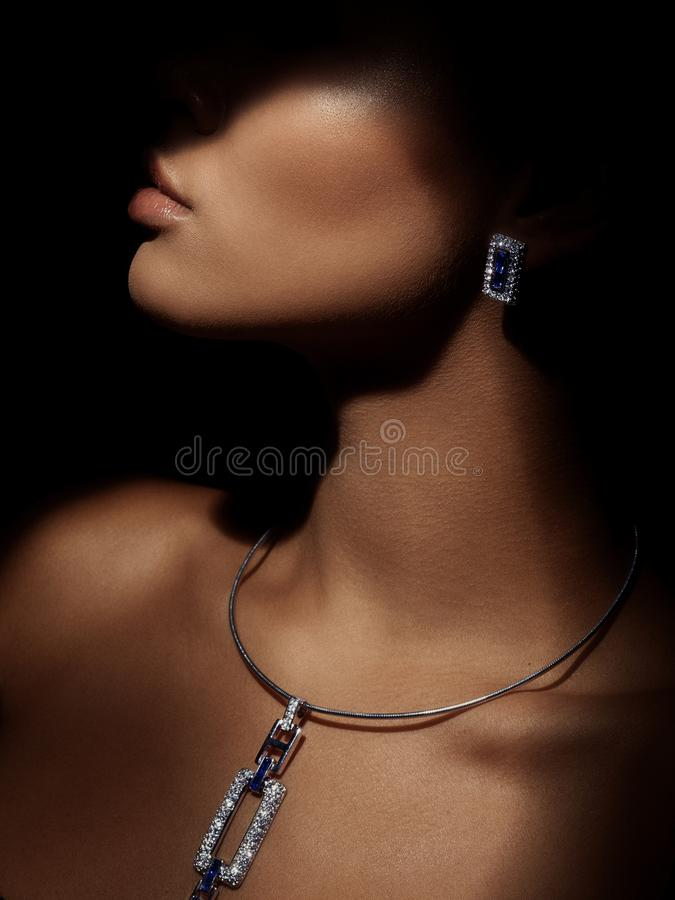 Portrait of an elegant and beautiful young smartly dressed woman with sparkling jewelry made from precious metals on her neck royalty free stock photos