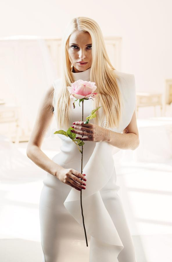 Portrait of an elegant blond lady holding a rose flower stock image