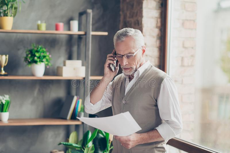 Portrait of elegant experienced old bearded professional successful qualified businessman talking on phone with businesspartners royalty free stock photography