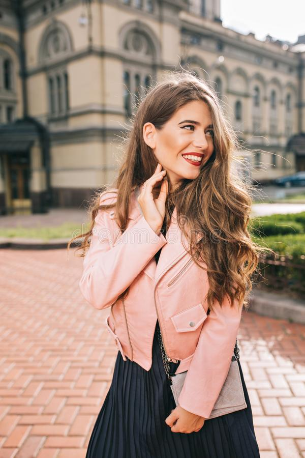 Portrait of elegant girl with long hair posing on street on buildings background. She wears black dress, pink jacket stock photos