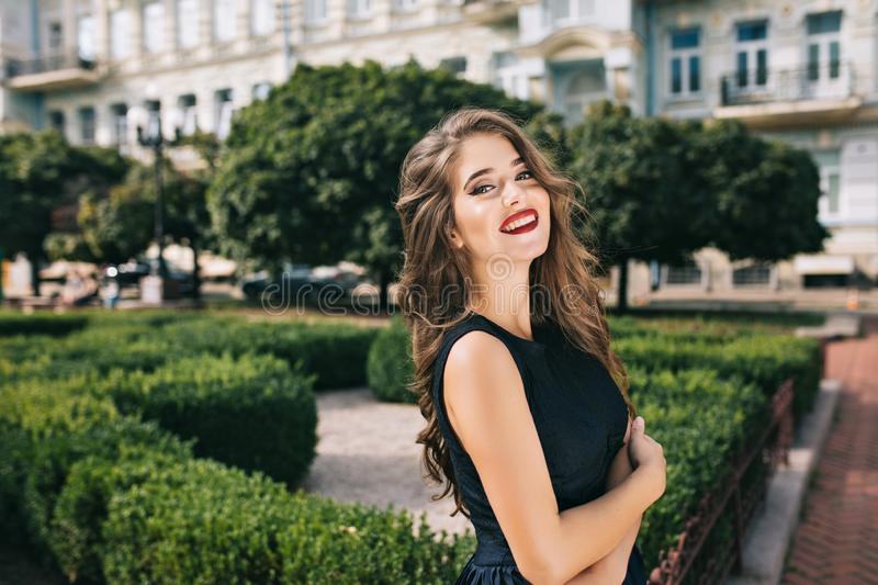 Portrait of elegant girl with long hair and vinous lips in coutyard. She wears black dress and smiles to camera royalty free stock photo