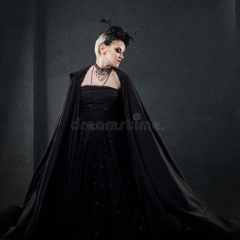 Portrait of an elegant Gothic blonde woman. Girl in wreath of black flowers and black cloak stock images