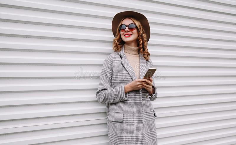 Portrait elegant happy smiling woman holding phone wearing gray coat, round hat looking away over white wall royalty free stock photo