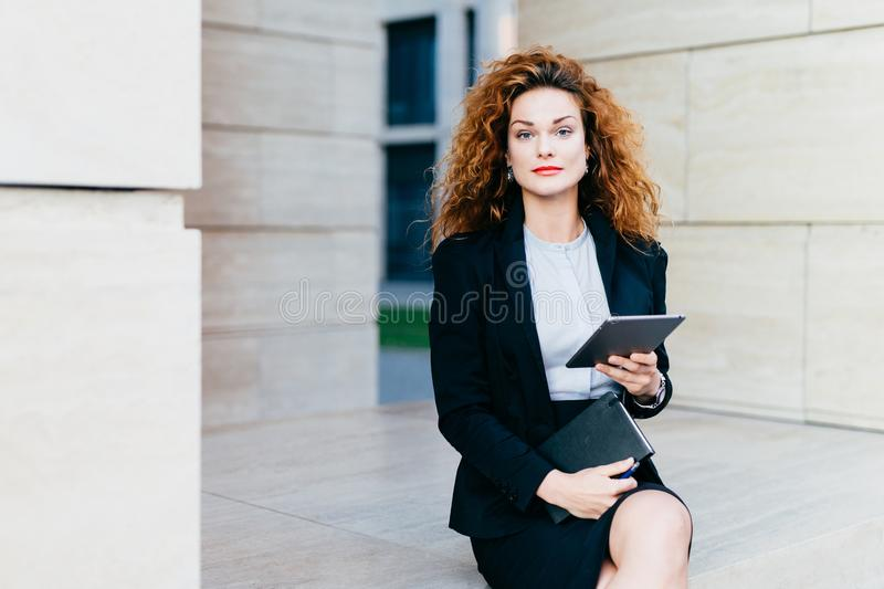 Portrait of elegant lady dressed in white blouse, black jacket and skirt, holding tablet and pocket book while sitting near office. Builduing. Successful stock photo