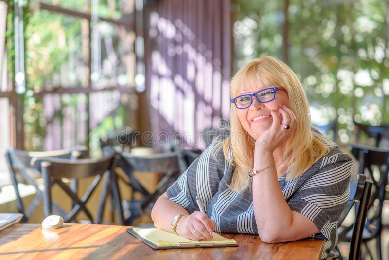 Portrait elegant middle aged plus size woman sitting and making notes to her diary on balcony or terrace of cafe. royalty free stock photography