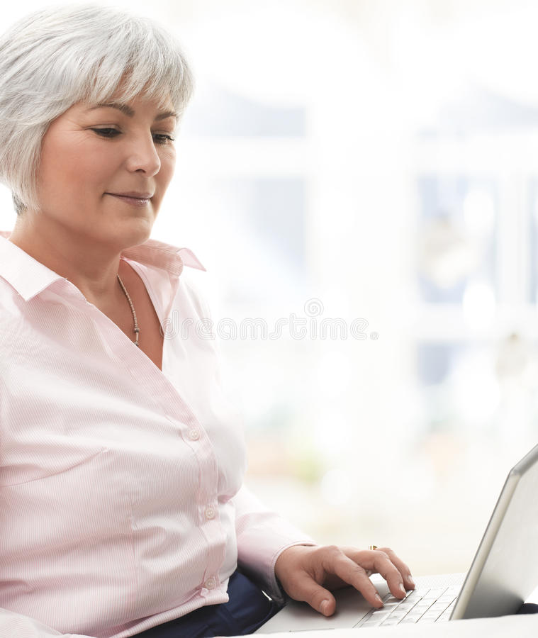 Download Smiling Senior Woman Working On Laptop Stock Photo - Image: 30067786